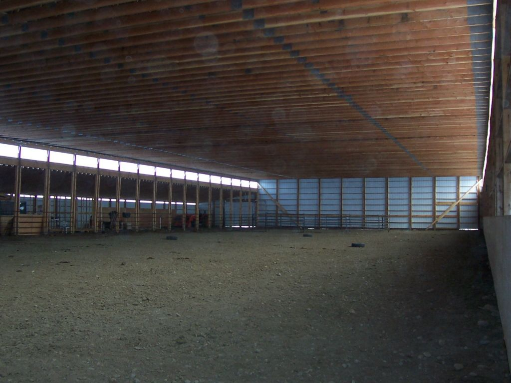 Exposed trusses overhead and stalls lining one side of a post-frame riding arena.
