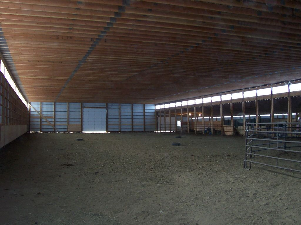 Interior of a riding arena with an overhead door on one end and stalls lining one side.