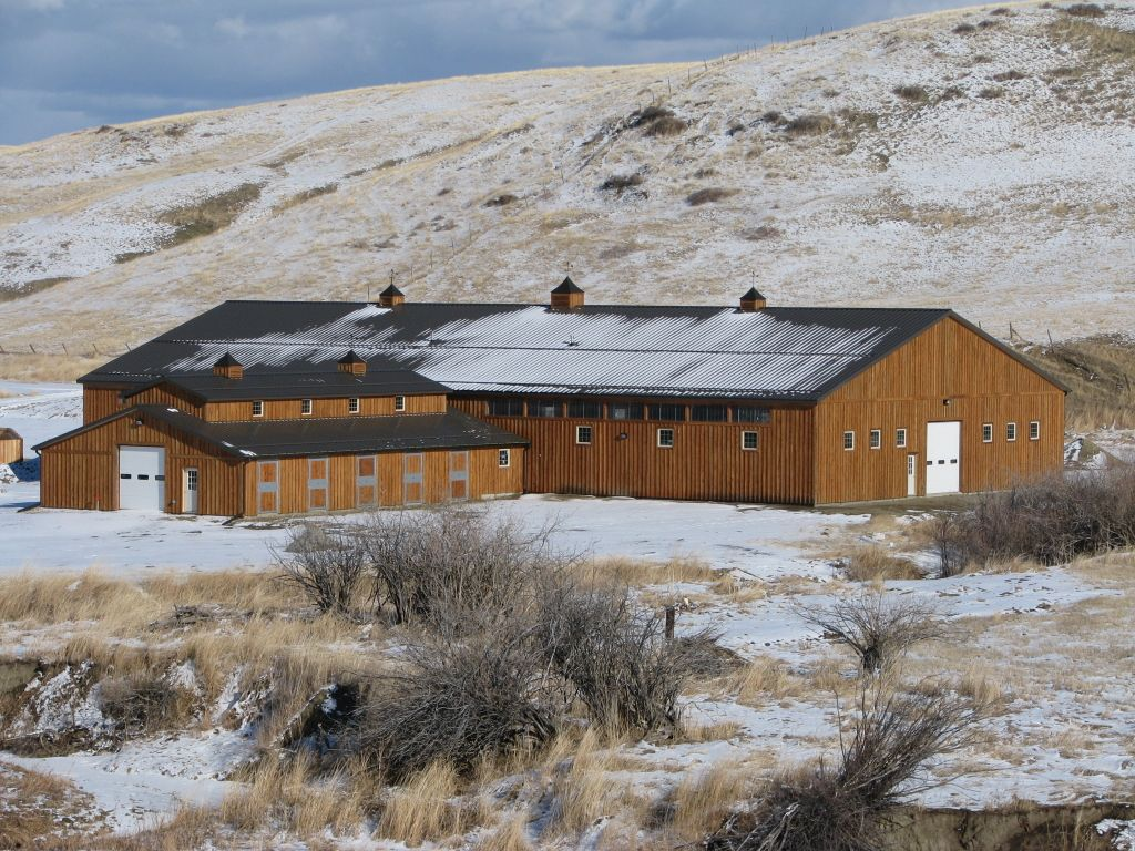Custom wood-sided riding arena and stable nestled amid snow covered hills.