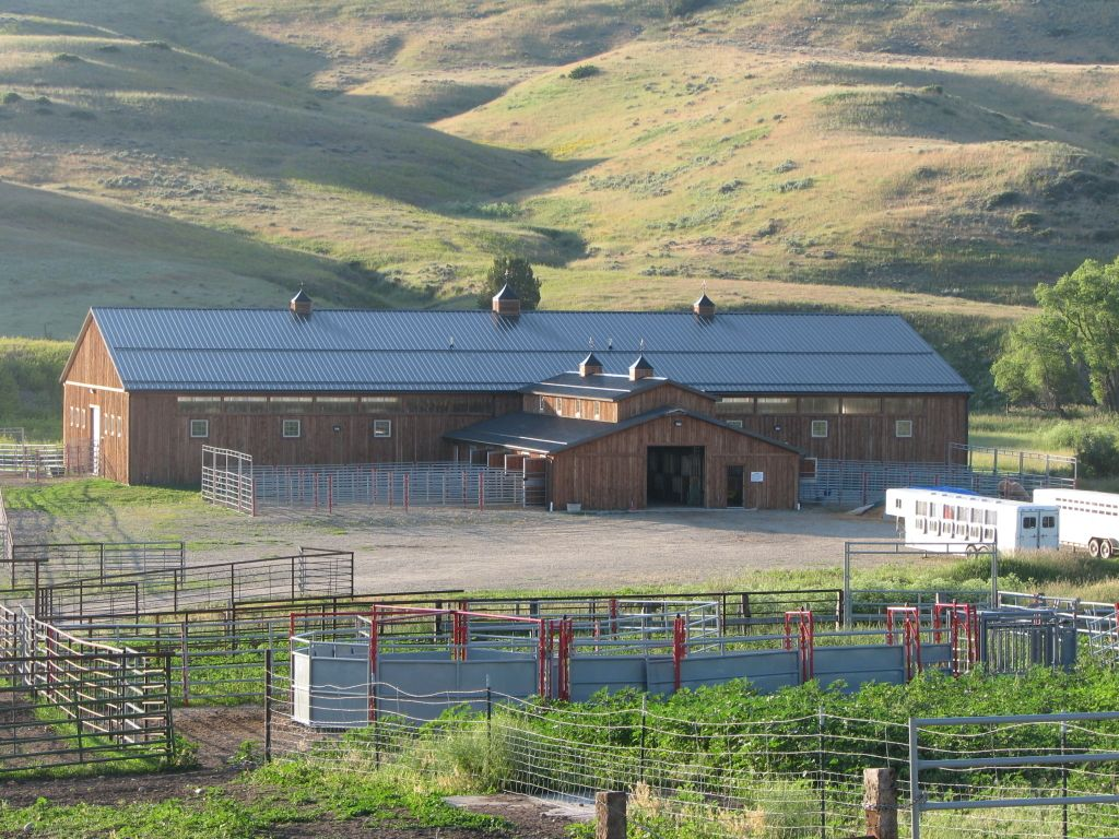 Custom wood-sided riding arena and stable nestled amid hills with paddocks in the foreground.