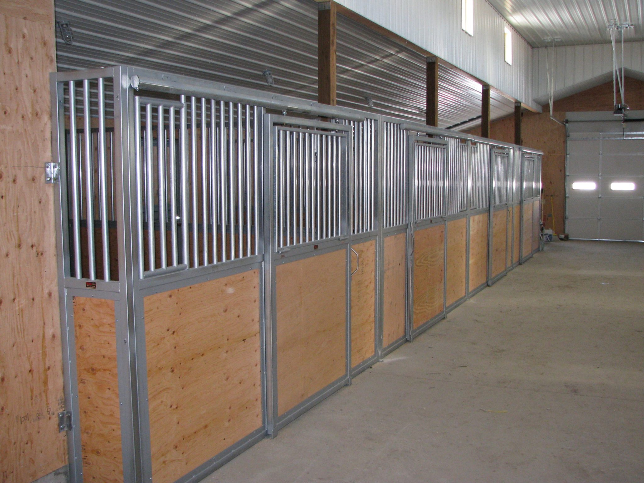 Wood and metal stall enclosures line one wall of a stable.