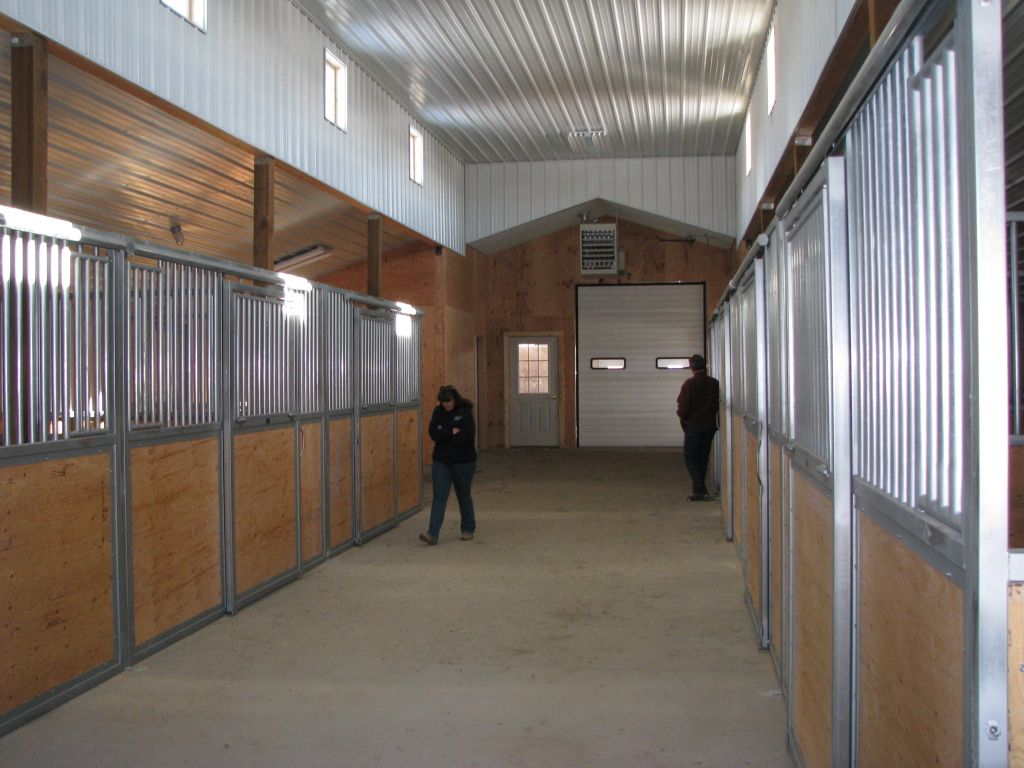Interior of stables with clerestory windows and wood and metal stall enclosures lining both sides.