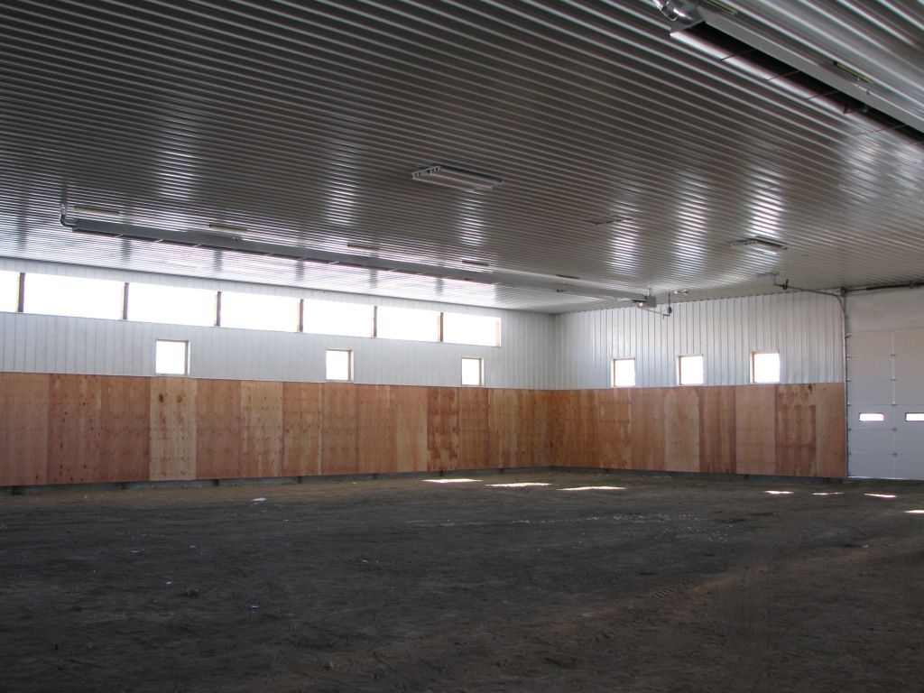Interior of riding arena that has white steel roof liner and ceiling mounted heaters.