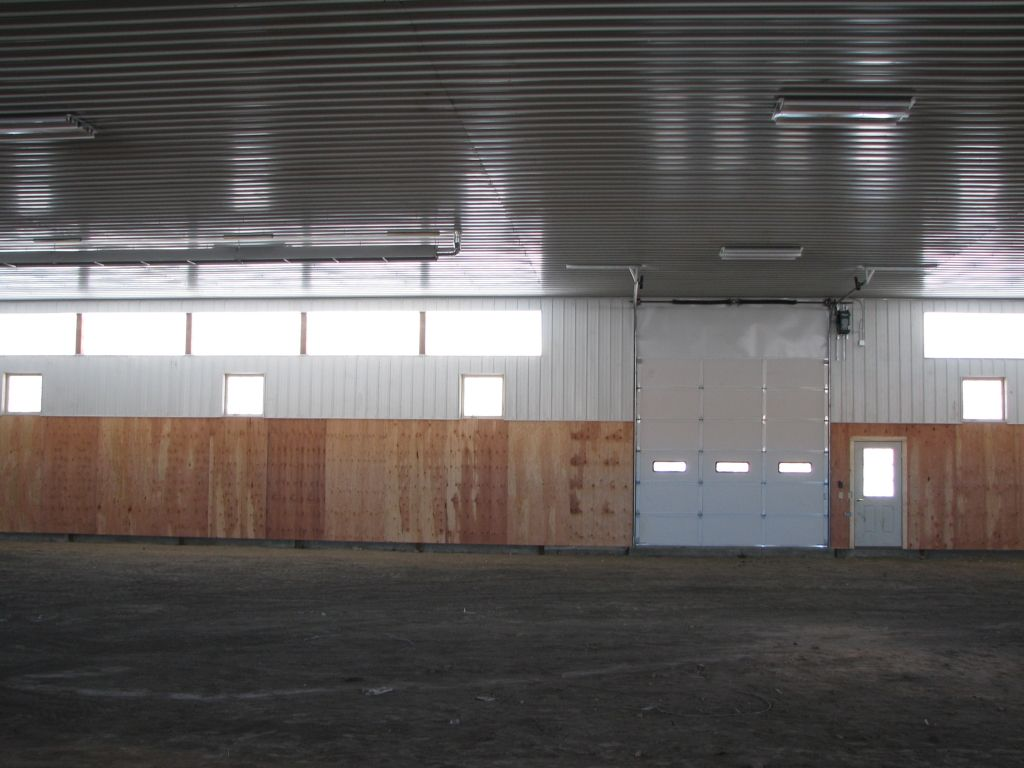 Interior of a riding arena showing an overhead steel door, entry door, windows, and fiberglass light panels.
