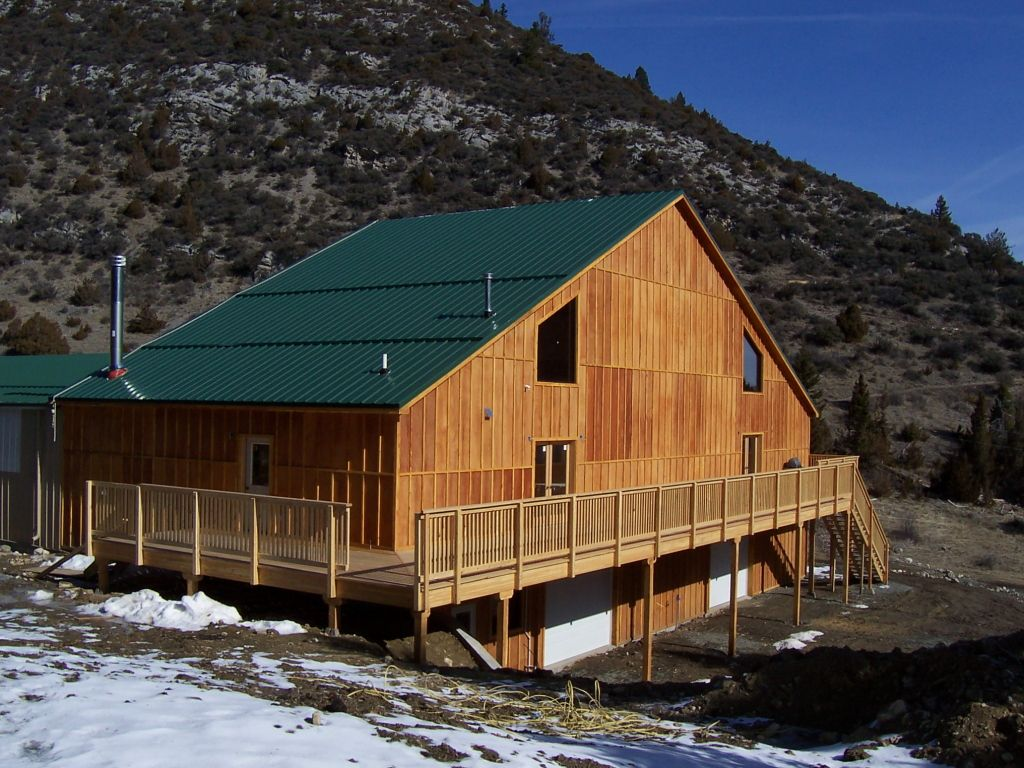 Exterior of riding arena observation room that has custom board and batten wood siding and green steel roof.