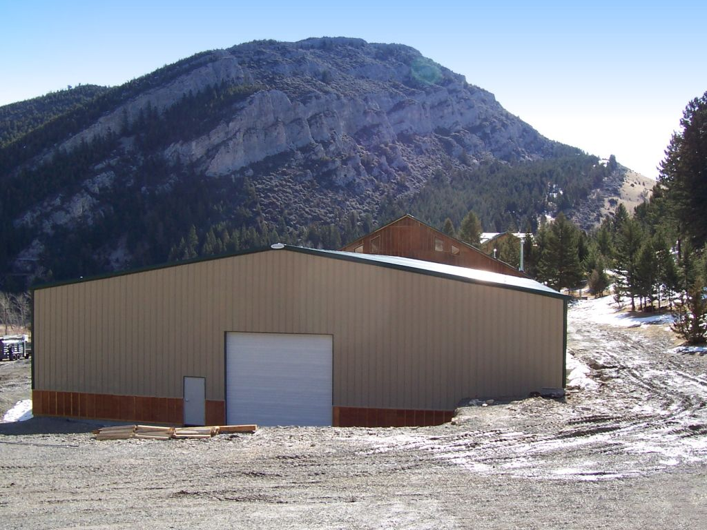 Gable end of a riding arena with a large overhead door and a walk door. Sided with tan steel and custom wooden wainscot.