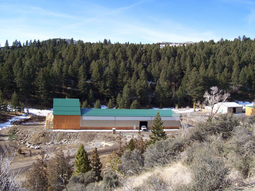 A green-roofed riding arena sits amid evergreen tree covered hills.