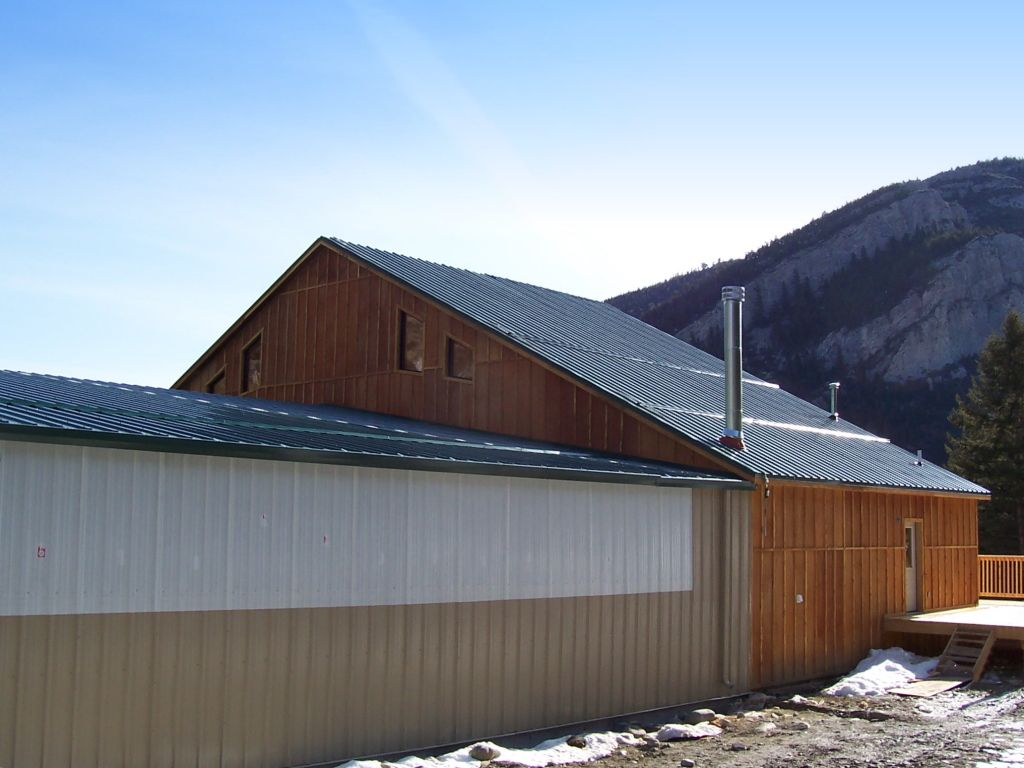 Gable roofed riding arena that has an attached observation building with a steeper pitched roof.