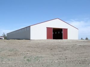Gable end of a post frame built riding arena with red sliding barn doors on one end.