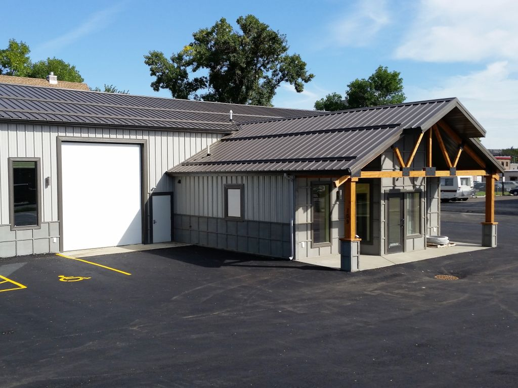 Commercial building with a portico covered entrance that has exposed trusses for details.