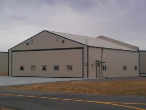 Exterior of a tan with green trim airplane hanger that contains a hydraulic lift door.