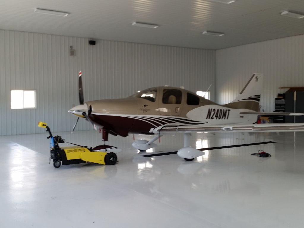 A small single propeller plane sits in a pristine white airplane hanger.