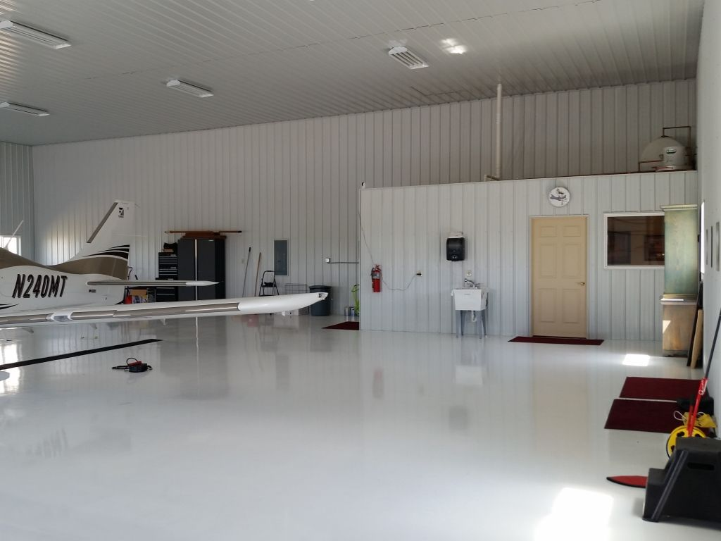 An enclosed office space in one corner of a pristine white airplane hanger.