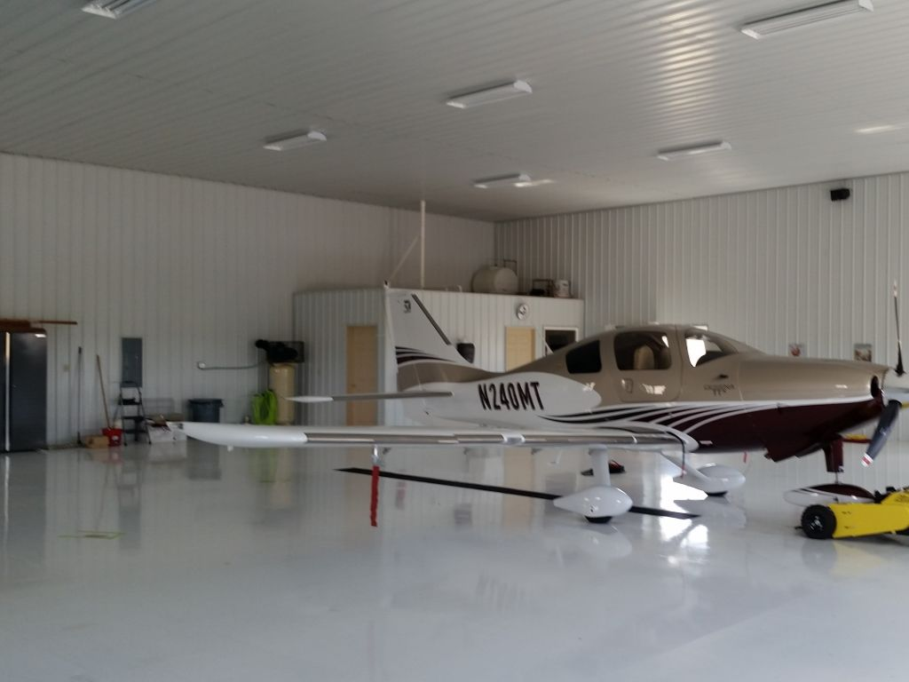 White steel walls and shiny white floor of the inside of an airplane hanger. An enclosed room is in one corner.