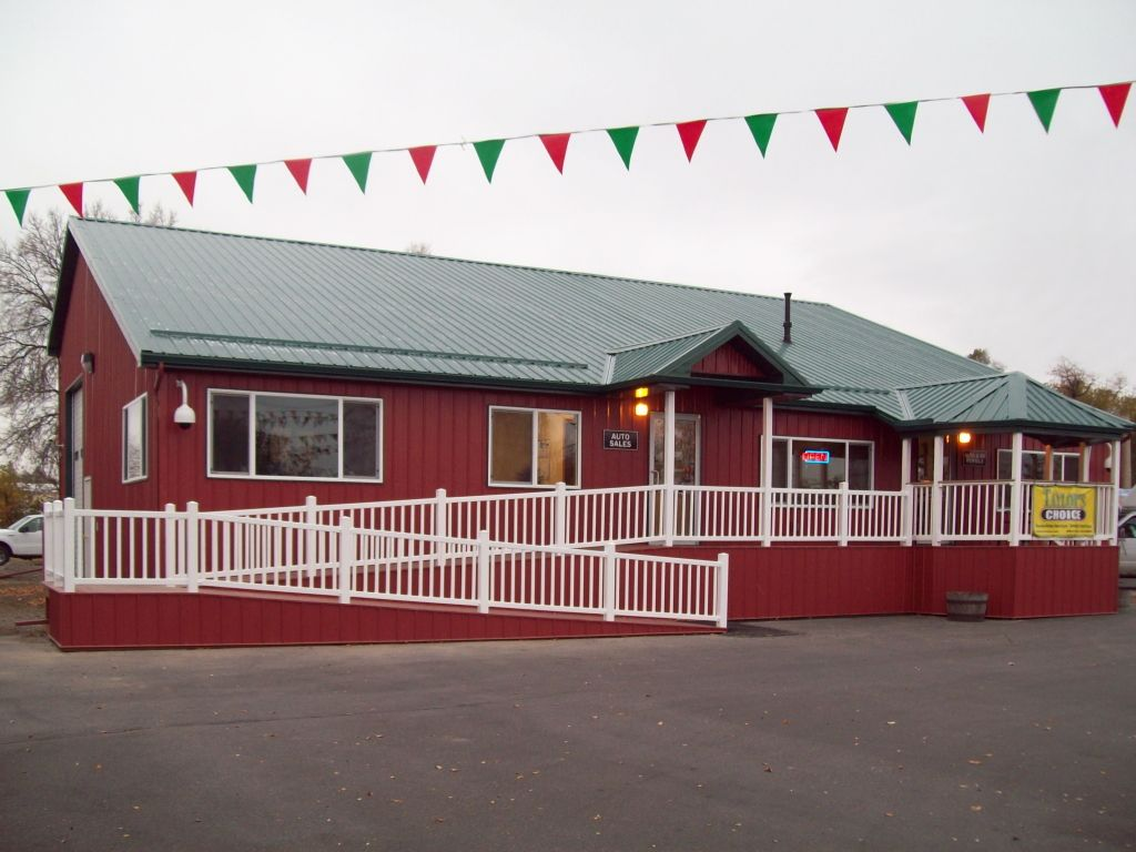 A red steel building built for a car lot office. A white-railed wheelchair ramp line the front.