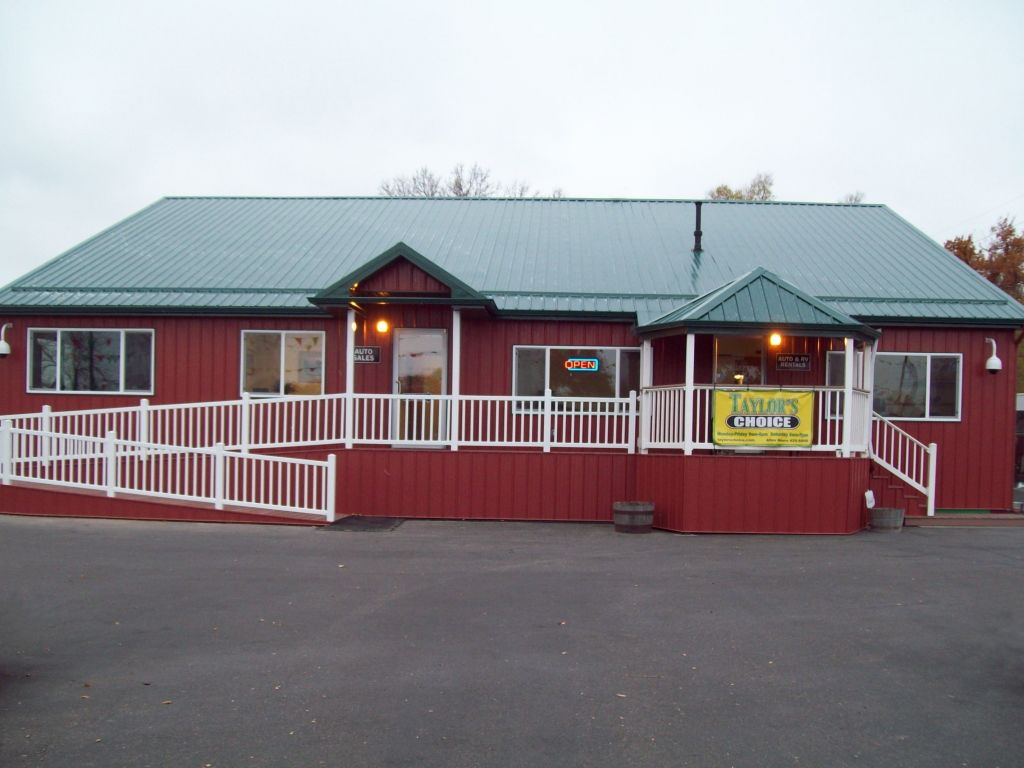 Front of a red steel building with a green steel roof. A wheelchair ramp and porch with white railing line the front.