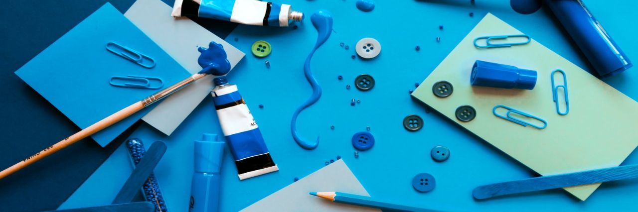 Craft supplies strewn across a desk, all in shades of blue.
