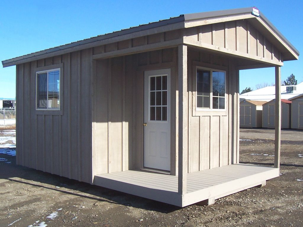 Cabin style shed that has a front porch, custom board and batten siding, and two windows.