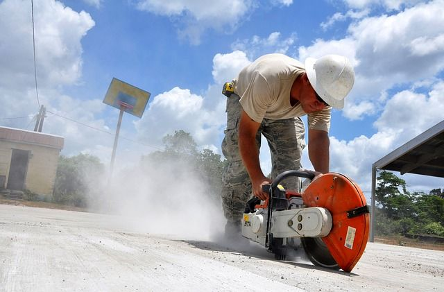 Man wearing a hard hat and using a concrete saw.