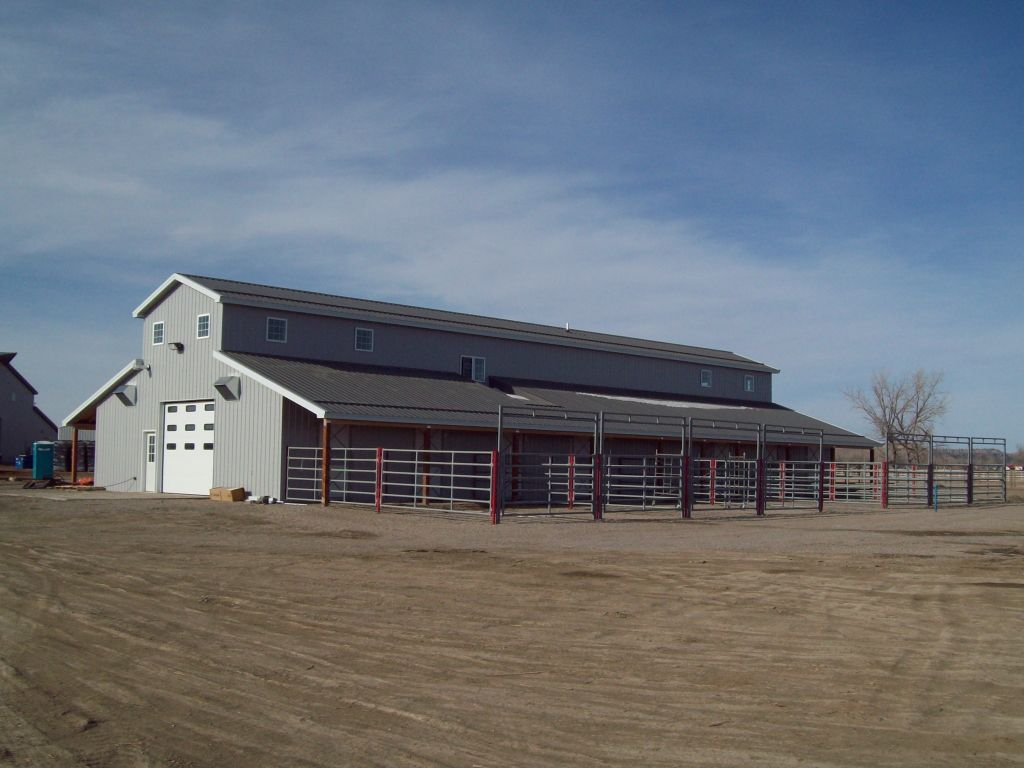 Gray steel post-frame barn with a monitor style roof and white overhead door on the end.
