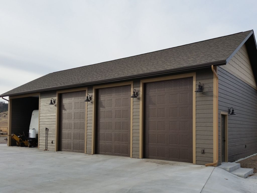 Far end of three car garage showing entry door and vintage looking lighting.