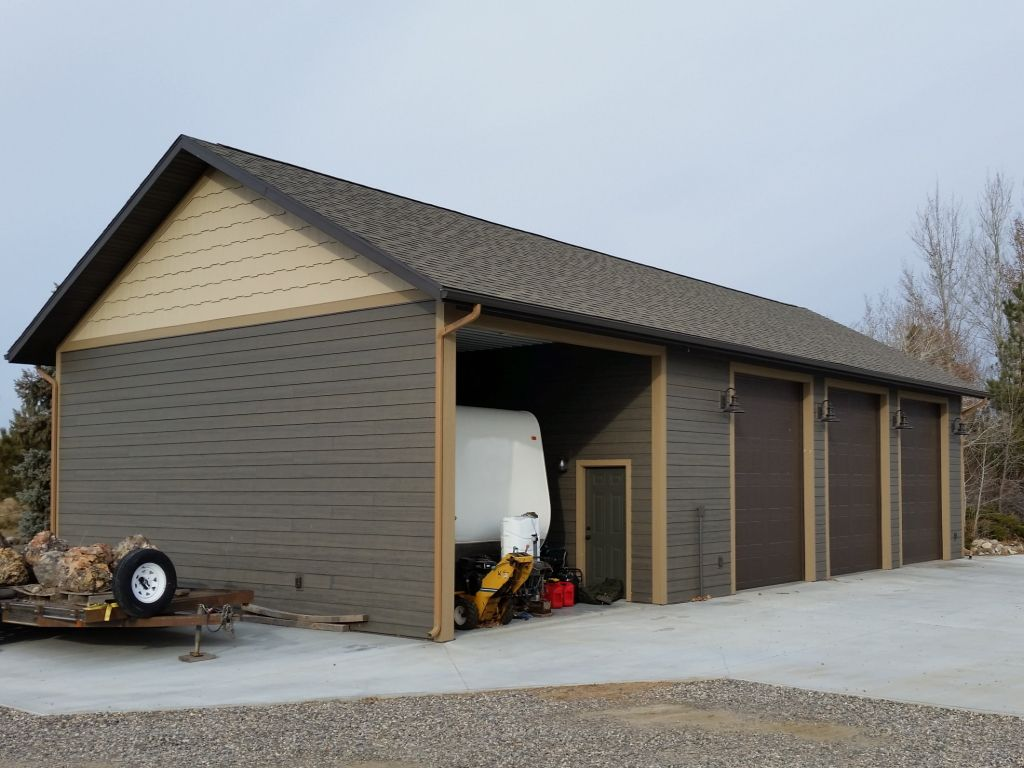 Three car garage with RV storage on the end. Shingled roof, lap siding and gable end siding detail.