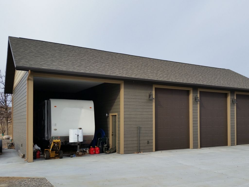 Open RV storage on one end of a garage that has brown lap siding, darker brown overhead doors, and a shingled roof.