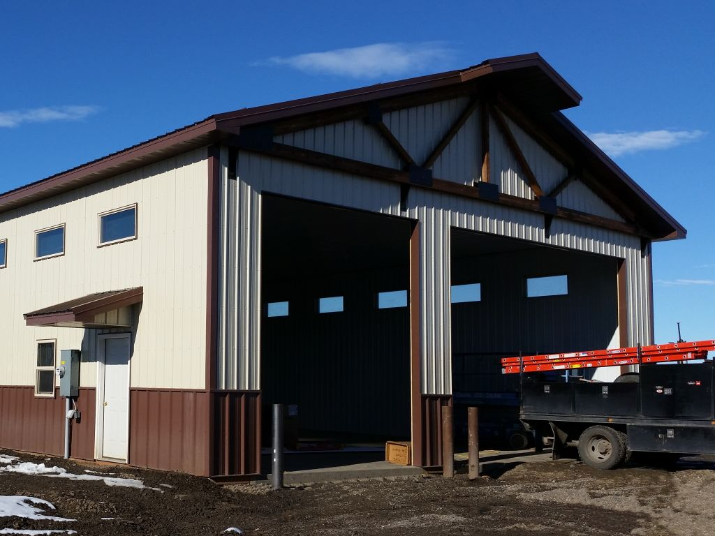 Post-frame shop building with exposed decorative truss above two overhead doors. Tan steel siding and brown steel wainscot.