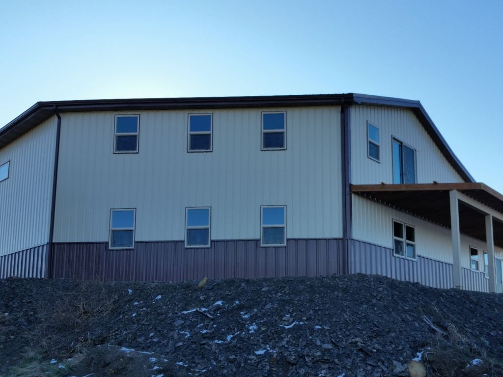 Two story post frame building with tan steel siding and brown wainscot.