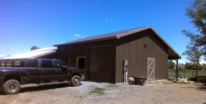 Brown steel siding on walls of a pole barn shop that has a brown overhead door.