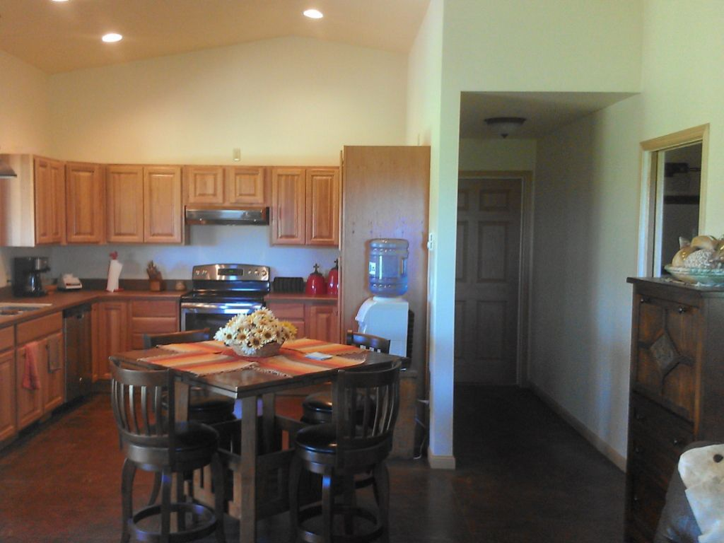 Interior of a post-frame building that contains a home. Wooden cabinets line the kitchen walls.