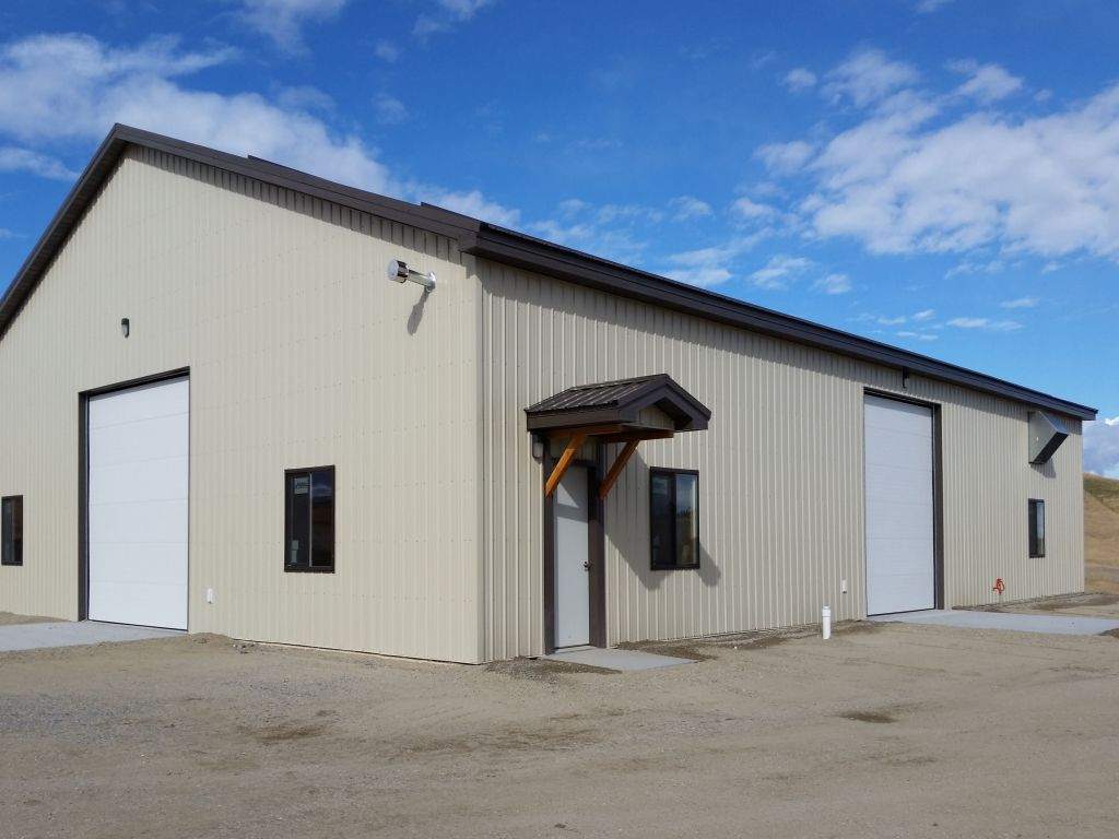 Gable awning covers an entry door on a steel-sided pole barn shop.