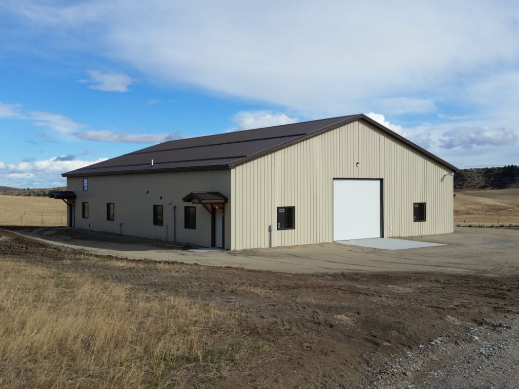 Gable roofed pole barn shop has an overhead door on one end and two gable awning-covered entry doors on one side.