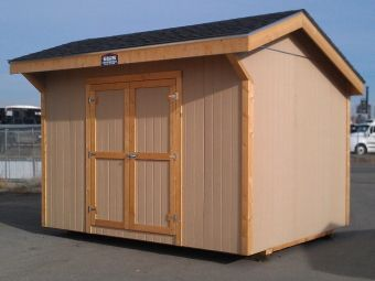 Pioneer style shed having an off center roof peak with overhanging eaves and the shed door on a sidewall.