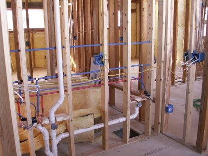 Framed internal wall that still has plumbing pipes and electrical wires exposed.