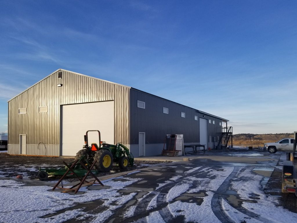 Gable end of pole barn with overhead doors and windows present.