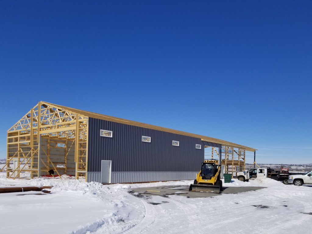 Pole barn under construction with steel on one side and exposed framing & rafters on the other.