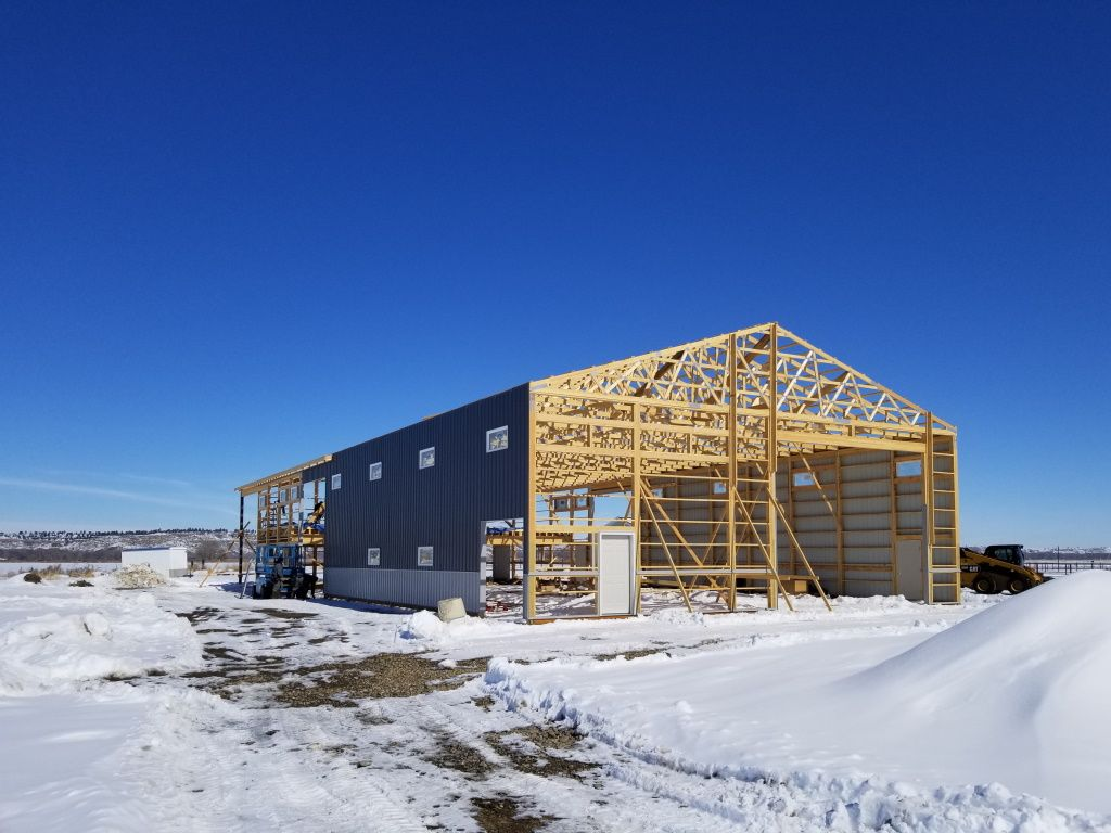 Construction of a pole barn with some steel siding put up and exposed framing visible.