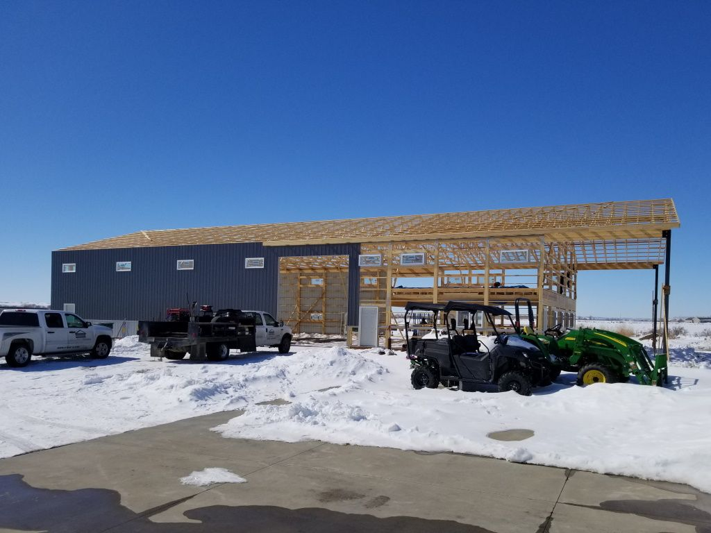 Pole building under construction with partially exposed framing and rafters.