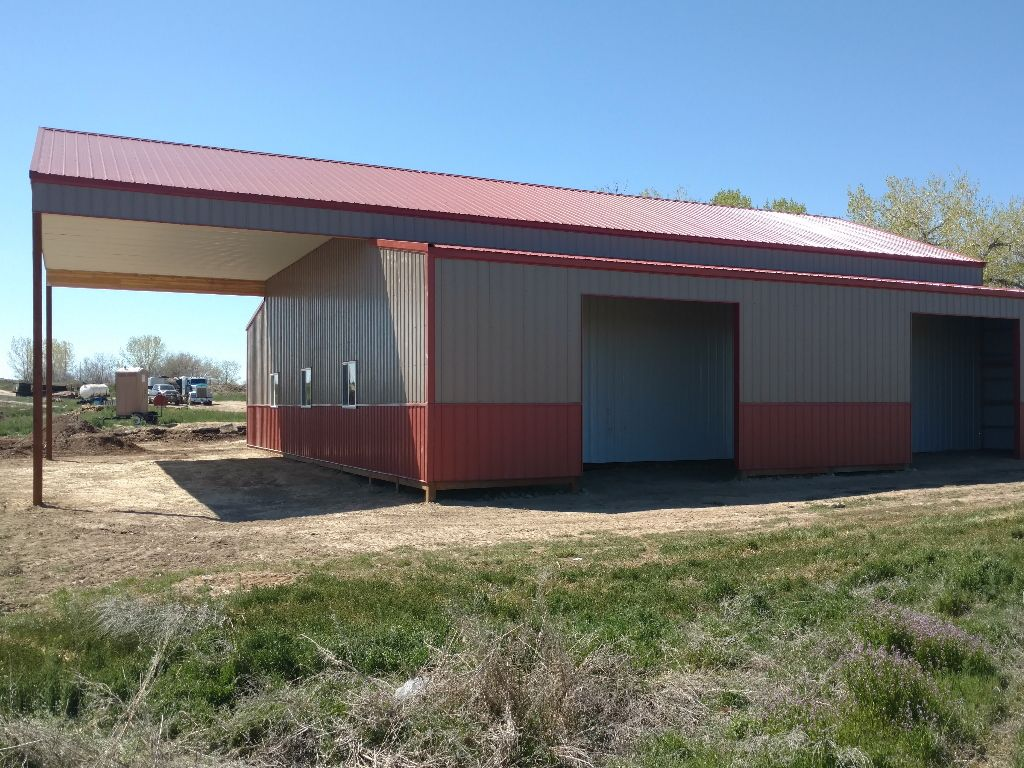 Pole barn with enclosed lean-to's on each side and extended roof on one end.