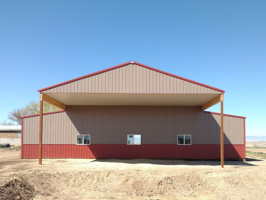 Gable end of a pole barn with a roof extension that creates covered area.