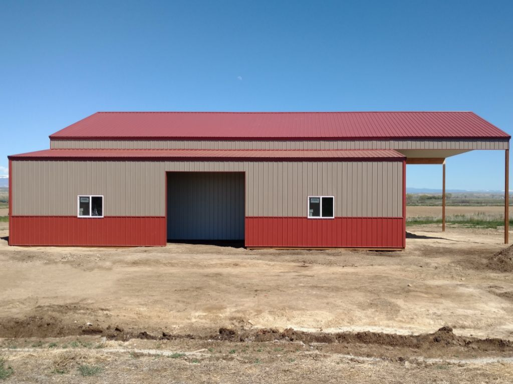 Side view of a pole barn with enclosed lean-to on the side and extended roof on the gable end.