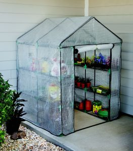 Portable clear plastic greenhouse with metal shelving.