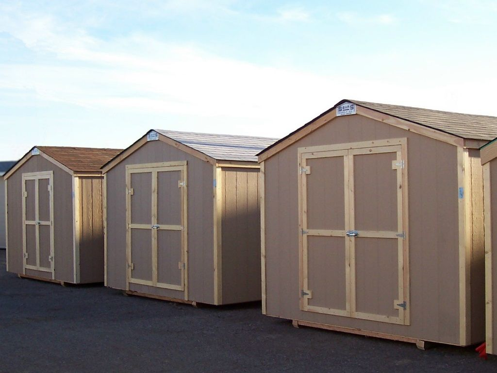 A row of sheds with gable roofs that has no overhang. All have hardboard siding and wood trim.