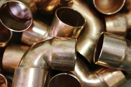 Jumbled bundle of 90 degree elbow fittings for copper pipe.