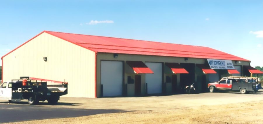 Series of overhead doors lining the side of a post-frame building that is covered with a red metal roof.