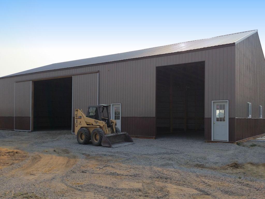 A pole barn containing a walk door, an overhead door, and a sliding barn door.