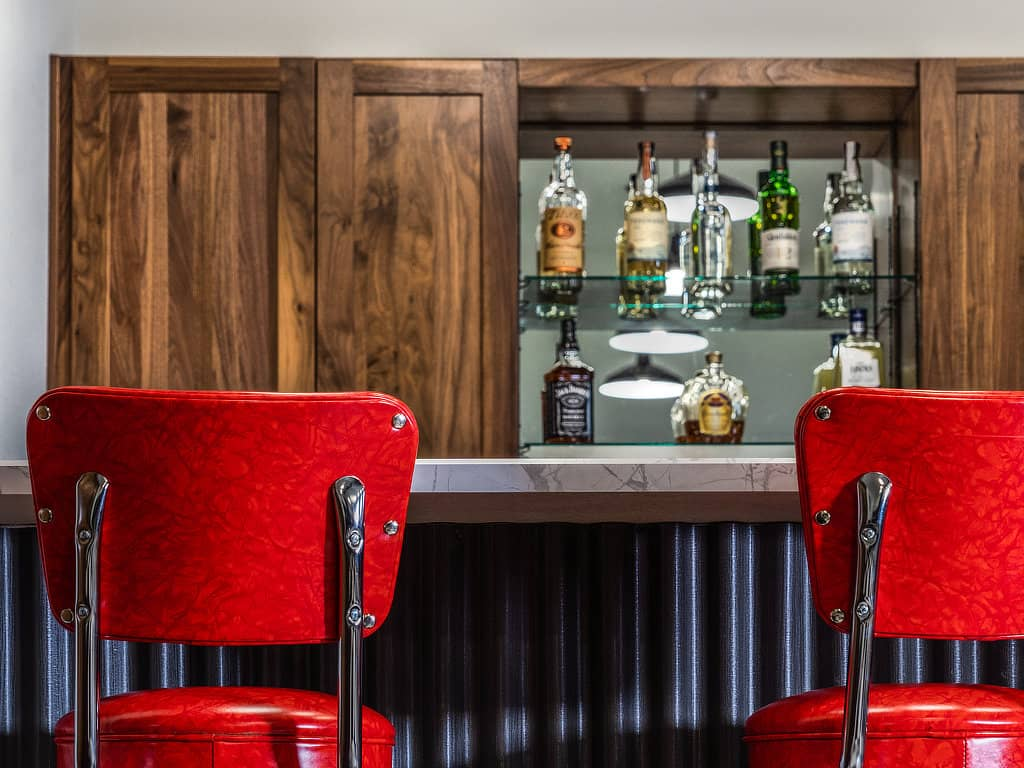 Red Barstools frame the corrugated metal wainscot and custom wood cabinetry in the background.