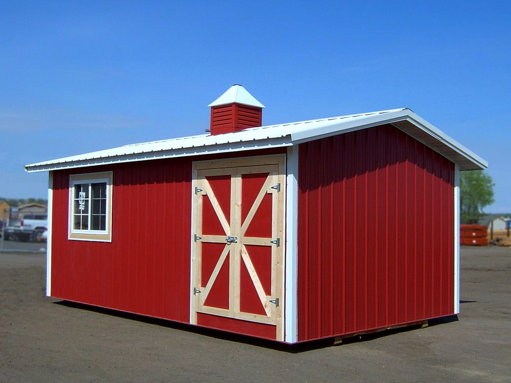 Red steel shed with white metal trim and roof. The shed roof is gable with overhanging eaves and a cupola on top.