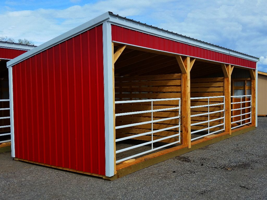 Red steel livestock shelter with stall divisions and white metal gates closing the front of each of three stalls.